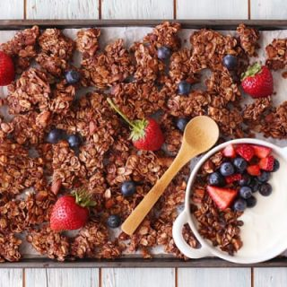 Chocolate granola on a baking sheet with fresh berries.