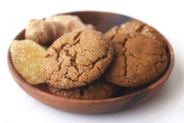 Cookies in a wooden bowl with fresh and candied ginger.
