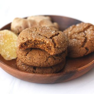 Triple ginger cookies stacked in a wooden bowl with a bite taken out of one.