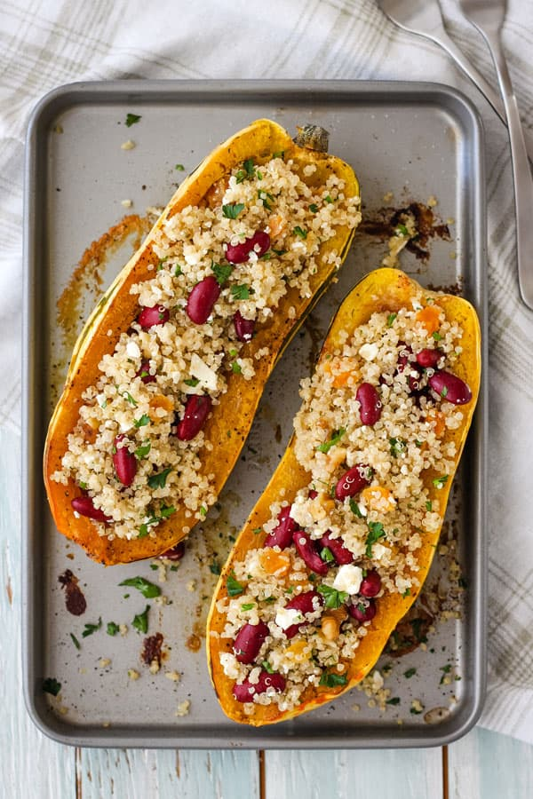 Two delicata squash boats stuffed with a quinoa salad on a toaster oven baking sheet.