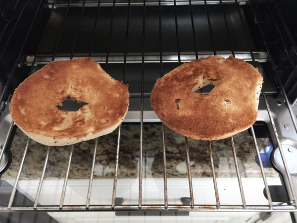 Toasted bagel slices on a toaster oven cooking rack.