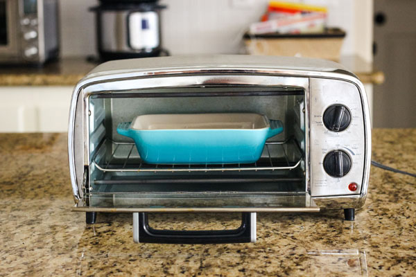 Blue 7x5 baking dish inside a small toaster oven.