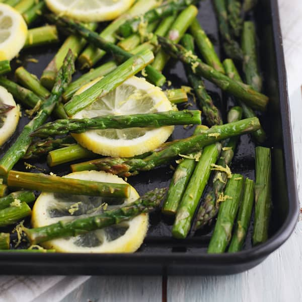 Toaster oven asparagus with lemons on a black roasting pan