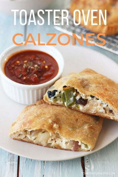 Toaster oven calzone on a plate with a cup of marinara sauce
