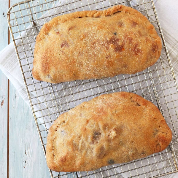 Golden baked toaster oven calzones cooling a rack.