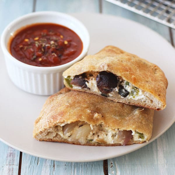 Warm toaster oven calzones on a plate with marinara sauce for dipping.