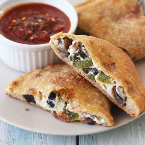 Crispy golden calzones with a side of marinara sauce on a plate.