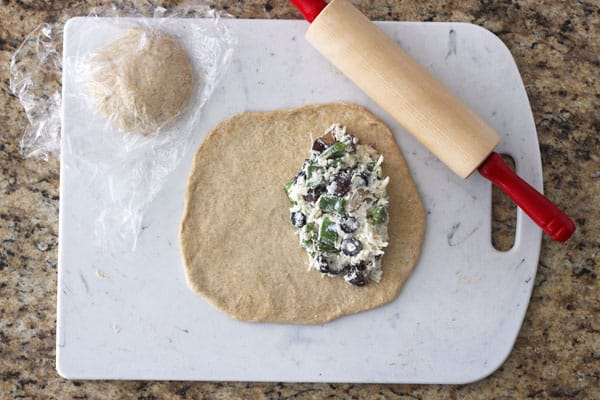 Rolled out dough with calzone filling on a cutting board.