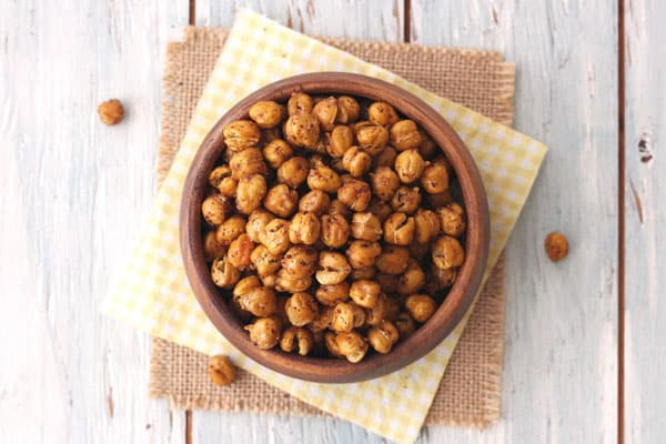Roasted chickpeas in a wood bowl with a yellow cloth underneath.