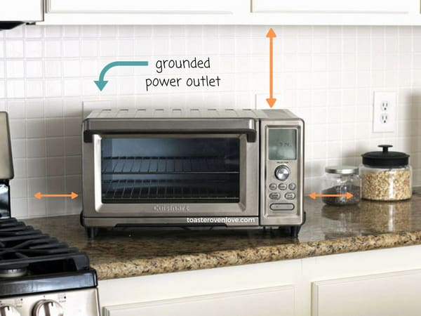 Toaster oven on a kitchen counter with arrows pointing to cabinets and outlet.