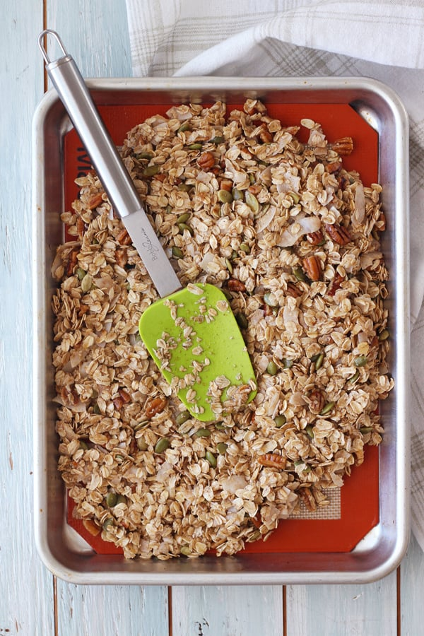 Uncooked granola pressed in a quarter sheet pan