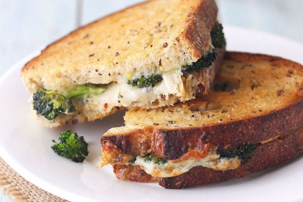 Grilled cheese with roasted broccoli inside on a white plate.