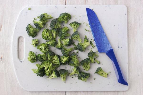 Raw broccoli florets on a cutting board with a blue knife.