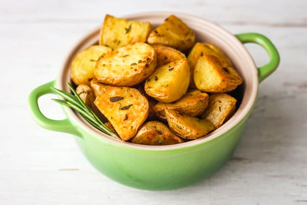 Buttery roasted potatoes in a small green oval baking dish.