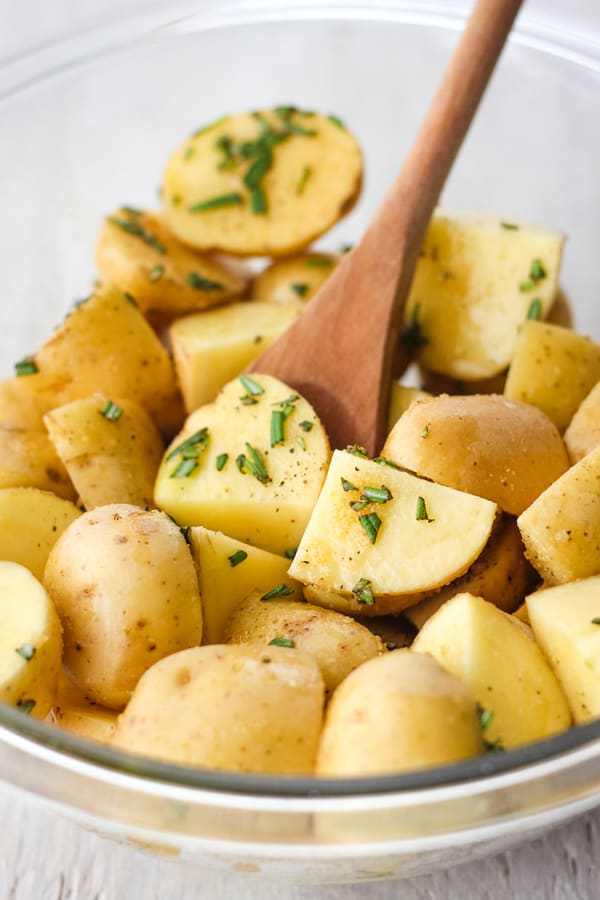 A glass bowl filled with chopped baby potatoes and fresh rosemary with a wooden spoon.