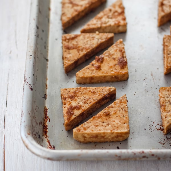 Tofu triangles on an oiled rimmed baking sheet.