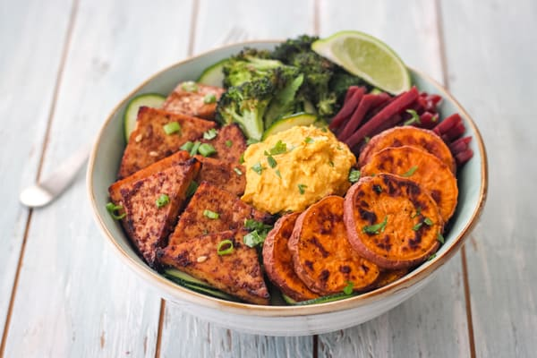 Broiled tofu in a large bowl filled with sweet potato rounds, broccoli and hummus.
