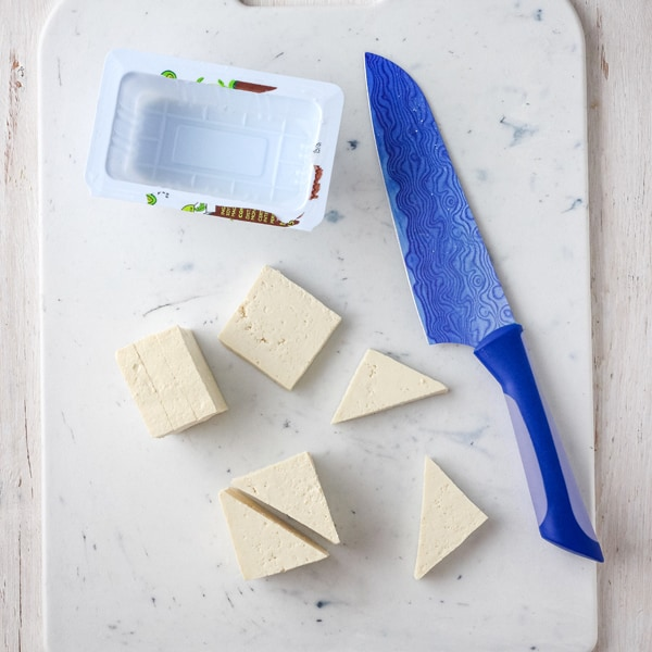 Drained tofu sliced into triangles on a cutting board.