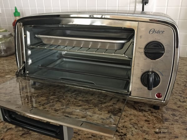 Little toaster oven with rack in top placement and set to broil.