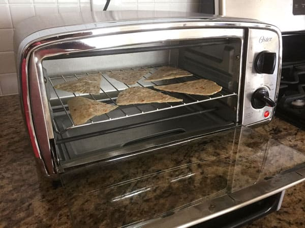 Flour tortilla slices baking on a toaster oven cooking rack.