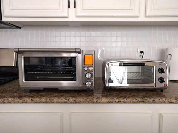 Large and small toaster ovens on a kitchen counter.